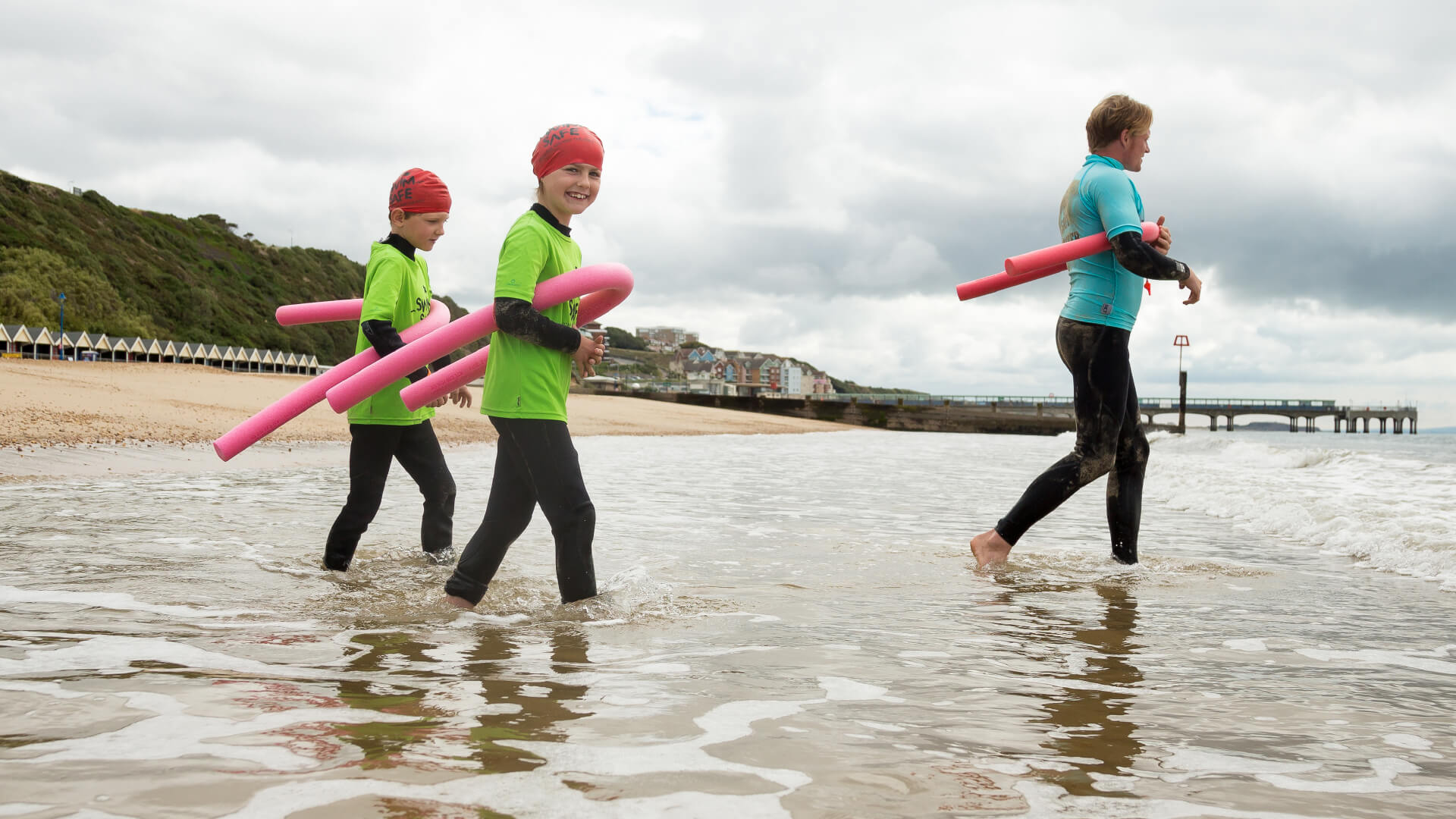 Two children and a swimming instructor in wetsuits walking into the sea