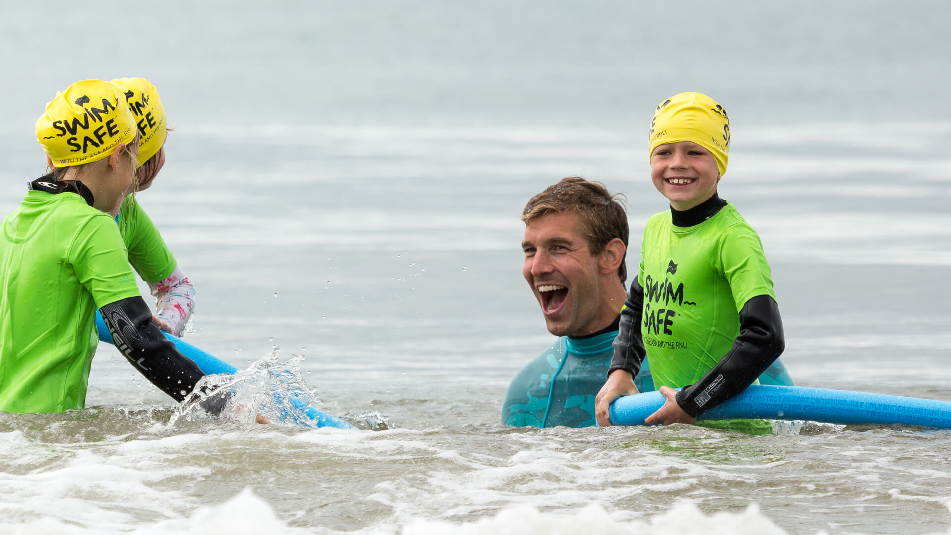 Three children having fun in the sea with a Swim Safe instructor in Boscombe, Dorset