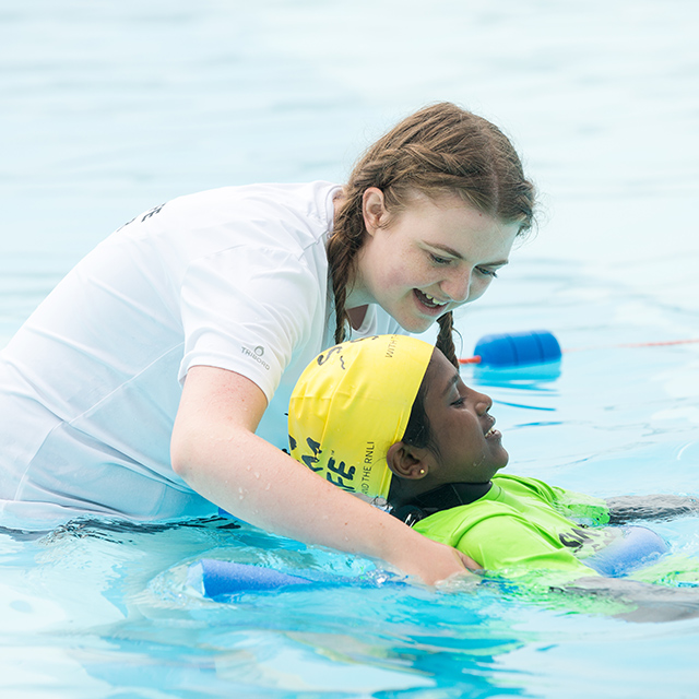 A Swim Safe instructor supports a young girl in Plymouth's Tinside Lido as she learns to float